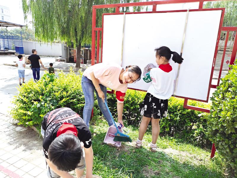 郊区实验小学40余名学生和家长走进桃花园小区清理卫生