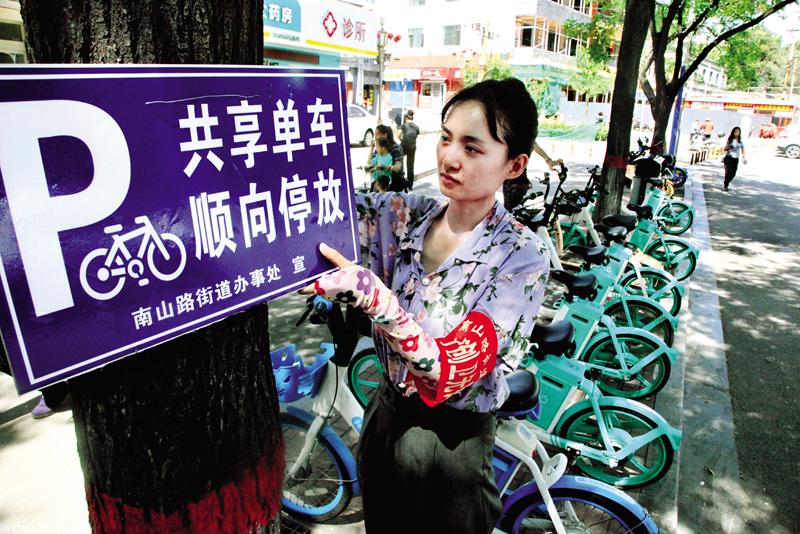 阳坡垴社区悬挂提示牌规范共享单车停放