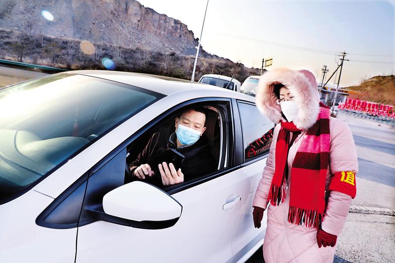 市农产品批发市场的工作人员对进入市场的车辆及人员进行疫情防控检查