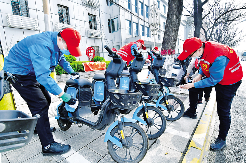 市自来水公司的青年志愿者对共享单车进行整理、擦洗