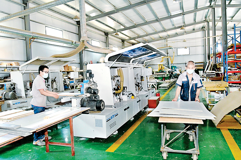 鹊山村扶贫产业园全屋定制生产区的工人在加工产品